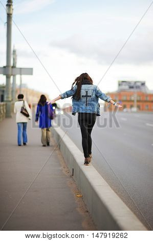 Brave girl in a blue denim jacket goes on the curb intently trying to keep his balance on a busy city street.