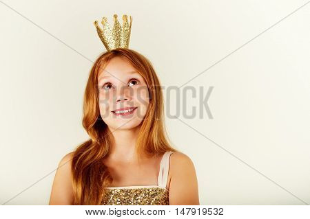 Pretty little girl with beautiful red hair looking up. Little princess with a crown on her head. Kids fashion. toned image