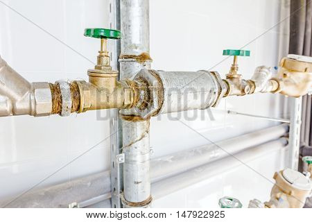 Water meters and valves in measuring place tiled room with white tiles.