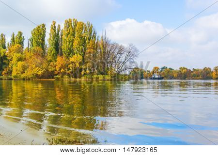 Scenic river landscape in sunny autumn day on a background of blue sky with white clouds