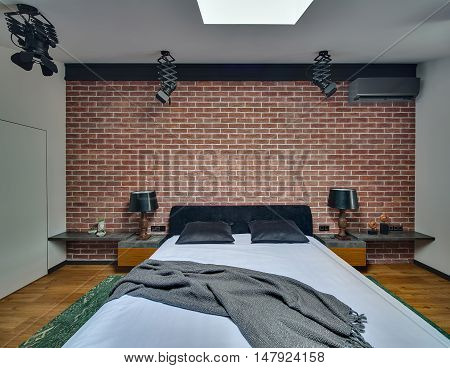 Cool bedroom in modern style with brick wall and parquet with green carpet on the floor. There is bed with pillows and coverlet, racks with lamps and decorations. At the top there are black lamps.