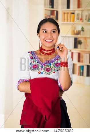 Beautiful young lawyer wearing black skirt, traditional andean blouse with necklace, standing posing for camera, holding red jacket, smiling happily, bookshelves background.