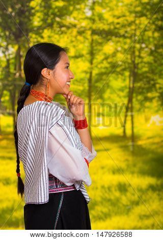 Beautiful young woman wearing traditional andean blouse with necklace, standing posing for camera, thoughtful body language and facial expression, green forest background.