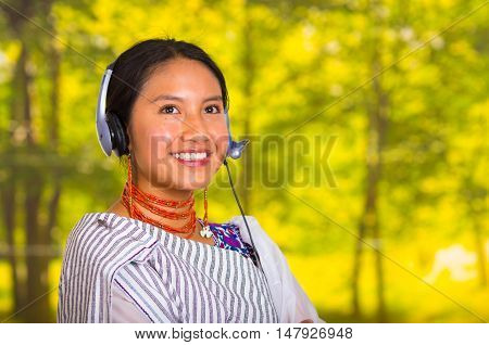 Headshot beautiful young woman wearing traditional andean shawl and red necklace, posing for camera with headphones smiling, green forest background.