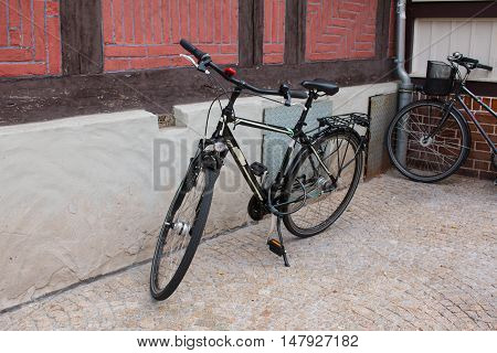 City Bicycle leaning against a house wall.