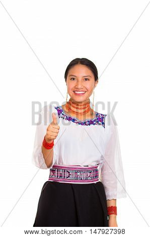 Beautiful young woman standing wearing traditional andean blouse and red necklace, giving thumb up while smiling happily, white studio background.