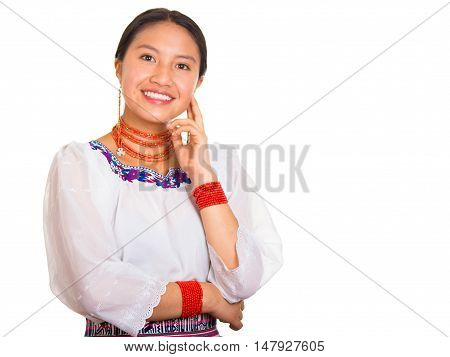 Beautiful young woman standing wearing traditional andean blouse and red necklace, resting head on hand while smiling happily, white studio background.