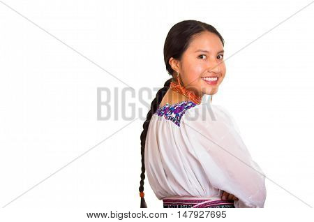 Beautiful young woman standing wearing traditional andean blouse and red necklace, turning head looking towards camera while smiling happily, white studio background.