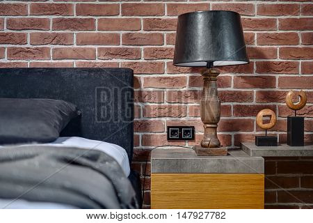 Old style wooden lamp with black lampshade on the rack on the brick wall background. On the right there is rack with decorations. On the left there is bed with pillow and coverlet. Horizontal.