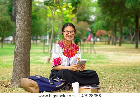 Young woman wearing glasses, traditional andean skirt and blouse with matching red necklace, sitting on grass next to tree in park area, relaxing while using tablet, smiling happily.
