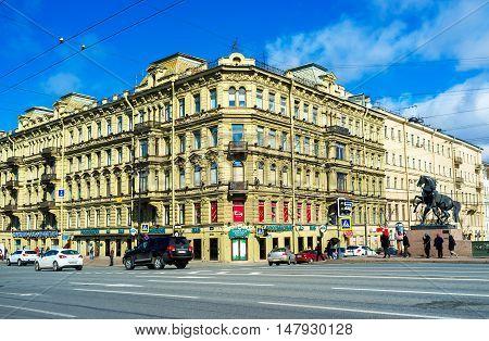 SAINT PETERSBURG RUSSIA - APRIL 25 2015: The beautiful mansions of Nevsky Prospekt with the Horse Tamer statue at corner of Anichkov Bridge on April 25 in Saint Petersburg.
