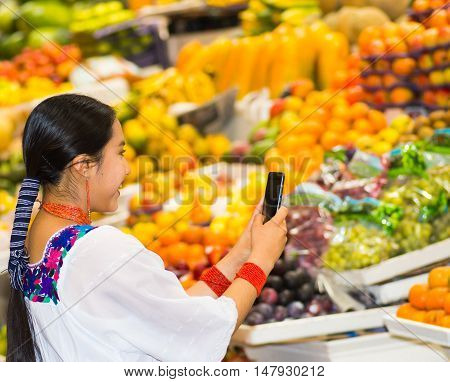 Beautiful young hispanic woman wearing andean traditional blouse using mobile phone taking pictures inside fruit market, colorful healthy food selection in background.