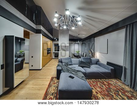 Modern style room with glowing chandelier and lamps. On the floor there is parquet with red carpet. There is mirror, wooden cupboard, kitchen island, table with chairs, blue sofa with pillows.