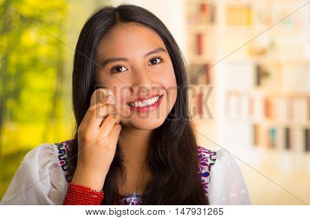 Beautiful hispanic woman wearing white blouse with colorful embroidery, using ponge applying makeup, smiling to camera.
