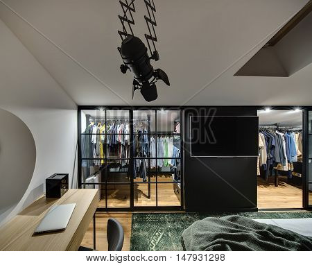 Elegant modern bedroom with cloakroom with glowing lamps, white walls. There is bed, table with laptop and chair, TV, window at the top. There are a lot of clothes in the cloakroom. Horizontal.