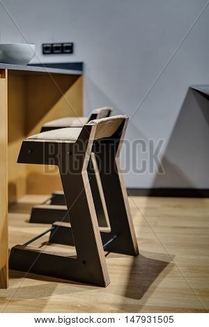 Couple of wooden stools which stands near the table on the gray wall background. Lamplight falls on them from above. There is white plate on the table. Close-up vertical photo.