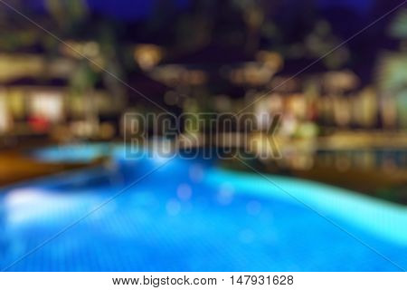 Blur night abstract background with resort hotel swimming pool reflective water surface. Blurry perspective view vacation summer party holiday relaxation pond