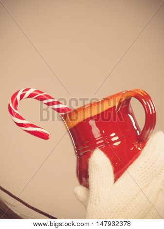 Young woman holding xmas mug with candy cane. Girls hands in woolen white gloves. Christmas time concept.
