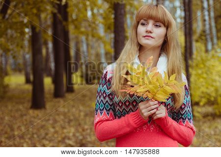 Girl in park colourful autumn. Holding vivid bouquet of foliage in hands