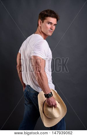 A hot sexy cowboy looks back at the camera.