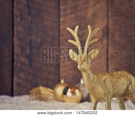 christmas gold reindeer decoration with wood background