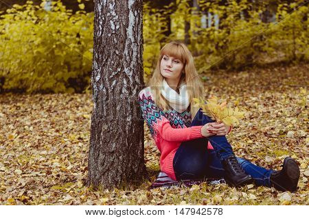 Fall concept - autumn woman sitting in park. Beautiful young modern woman smiling happy and cheerful