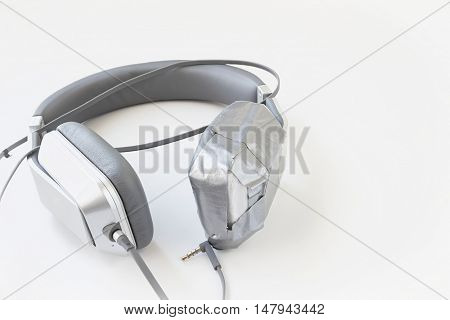 horizontal image of a pair of broken headphones that have one ear piece taped up with duct tape isolated on white background.