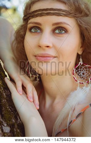 Beautiful Boho Girl Sitting against Tree. Beauty Concept