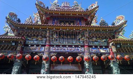 Buddhist temple with colorful details and red lanterns.