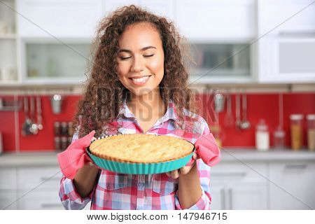 Beautiful African girl with cake in kitchen