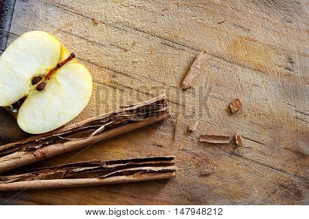 Apple and cinnamon on a wooden board, perfect for illustrations cusine and pastry