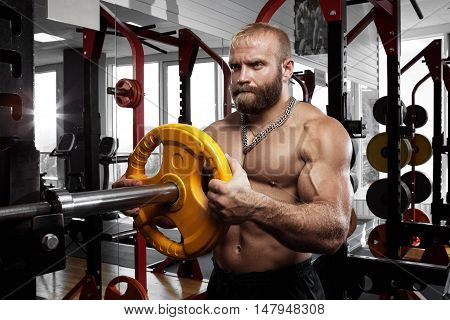 Handsome male bodybuilder prepares to do exercises with barbell in a gym holding barbell plate in hands.