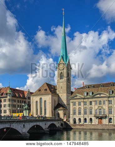Zurich, Switzerland - 4 September, 2015: people on the Munsterbruecke bridge, the Limmat river and the Fraumunster Cathedral. Zurich is the largest city in Switzerland and the capital of the Swiss canton of Zurich.