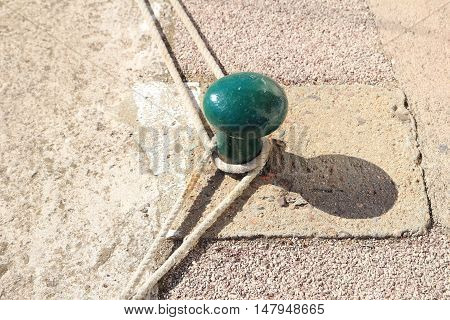 Green bollard on stone quayside with ropes mooring sailing boats