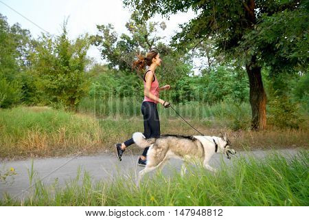Woman walking with husky in park