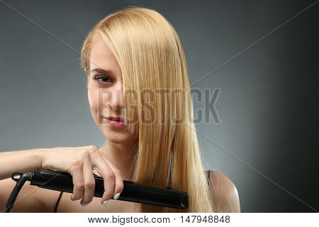 Fashion model girl straightening her hair on grey background