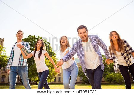 Five Cheerful Best Friends Holding Hands And Having Fun