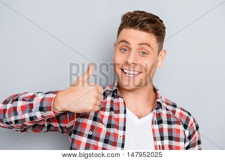"Portrait Of Young Toothy Man Showing ""like"" Gesture"