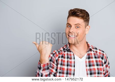 Happy Handsome Young Man Showing Direction With Finger