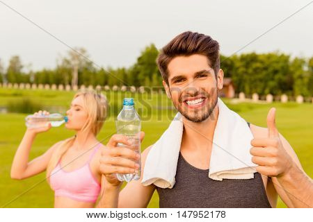 Smiling Man With Bottle Of Watter Showing Thumb Up. His Girlfriend Drinking Behind Him