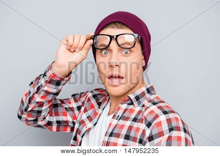 Portrait Of Shocked Young Man In Hat And Glasses With Open Mouth