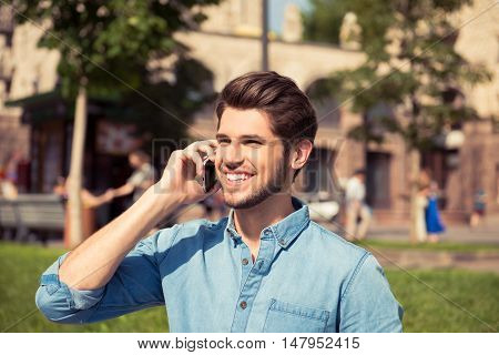 Portrait Of Happy Smiling Guy Talking On Phone In The Park