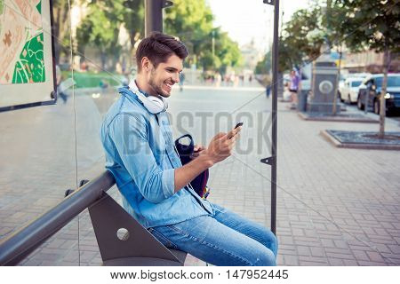 Young Stylish Man With Headphones Sitting On Bus Stop And Typing Sms