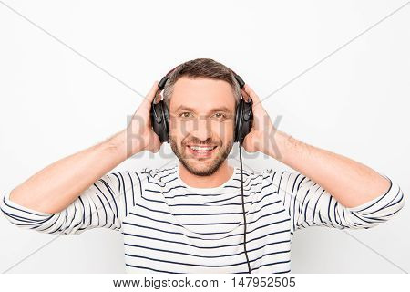 man listening to music and smiling on a white background