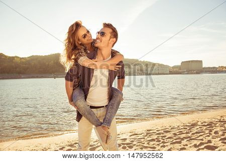 Portrait Of Two Happy Lovers. Man Piggybacking His Girlfriend