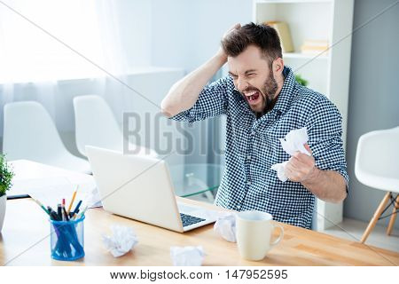 Angry Crazy Bearded Businessman Yelling And Crumpling Paper On His Workplace