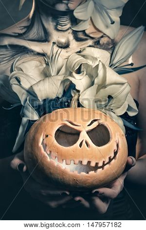 Jack-o'-lantern. Pumpkin close up in the hands of women. Young attractive girl with creative make-up for Halloween. Mysterious and frightening image of lilies. Witchcraft. Horrible.