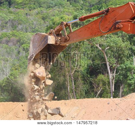 rustly orange bulldozer shovel arm, seen releasing a load of rocks, forest in the background, Songkhla, Thailand