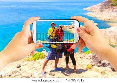 Smartphone photographing Asian lover couple at Similan Island Koh Ta Chai Andaman Sea Thailand