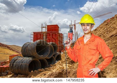 Asian young man worker of construction city project on working site background. heavy industry concept